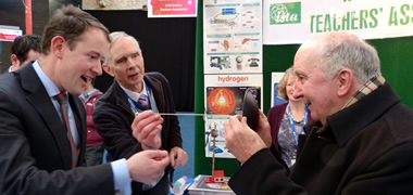 Minister Sean Sherlock T.D. visiting the ISTA stand at the BT Young Scientist & Technology Exhibition with Rory Geoghegan and Paddy Daly presenting a physics phenomenon.