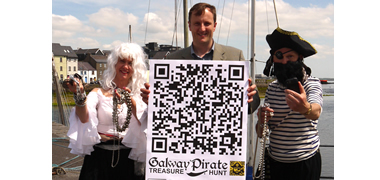 Dr Brian Wall, Digital Enterprise Research Institute, at NUI Galway, helps Pirates Hazel and Paul from Galway Simon launch their QR Code Treasure Hunt which takes place during Volvo Ocean Race Week in Galway.